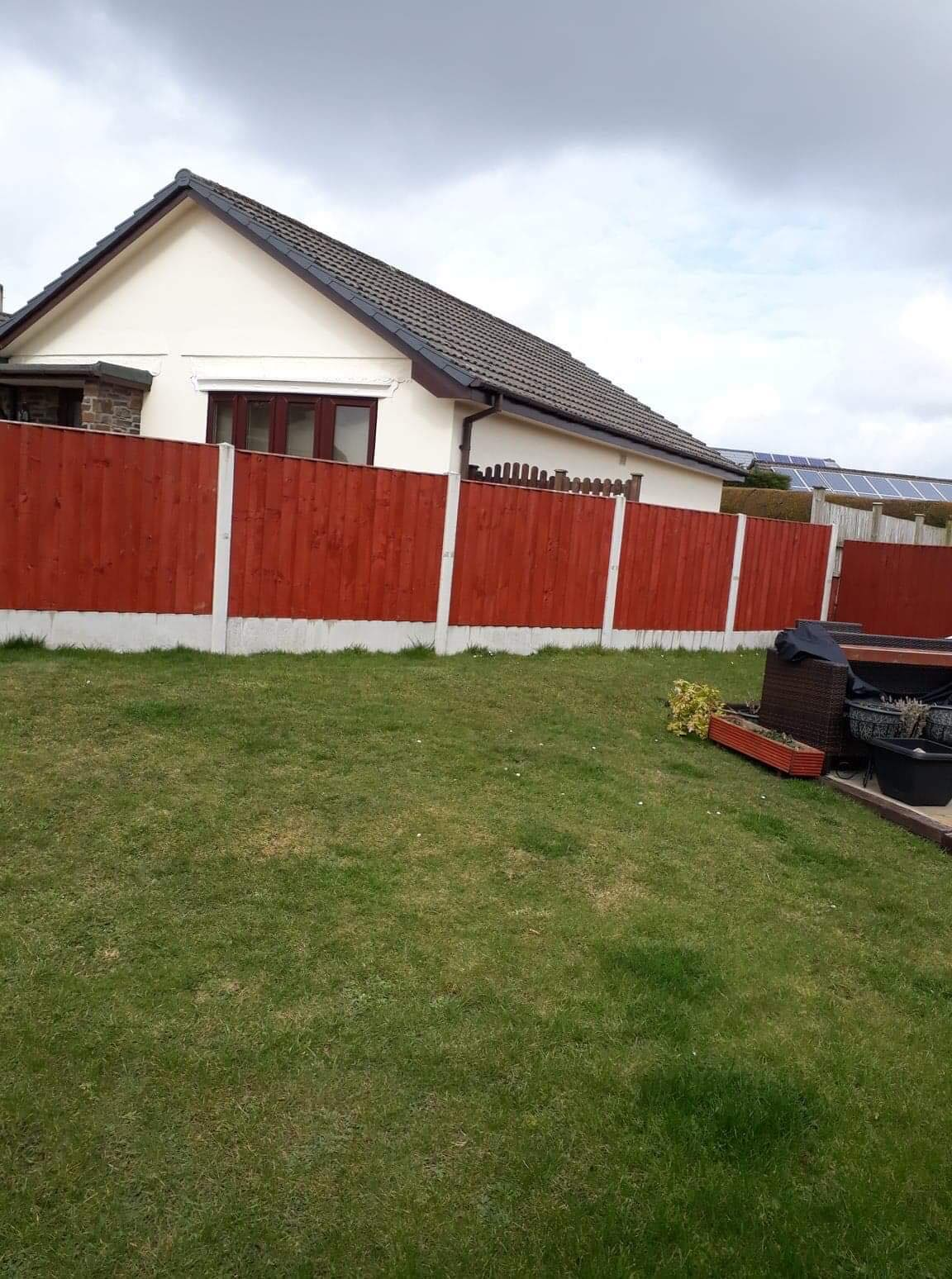 Stained panel fencing in concrete base. Dramatic colouring against the green grass.