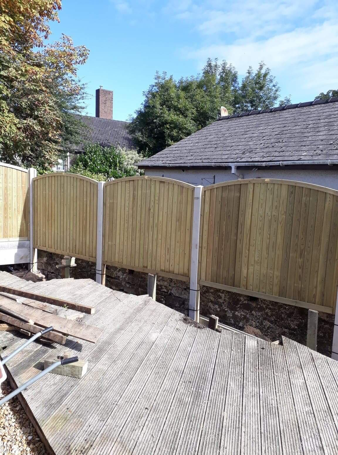 panel fencing in concrete base, the top of the panels are curved beside decking.
