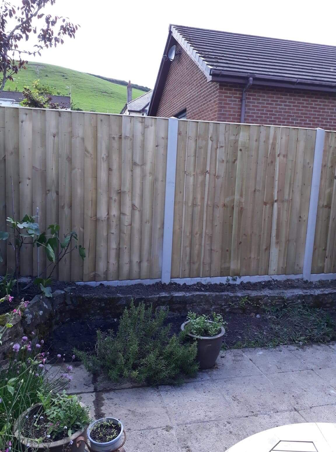 Straight edged top of panel fencing in concrete base. Prior to planting border.