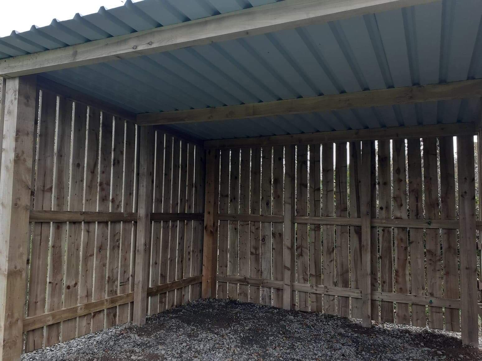 Wooden feed shed with corrigated roof.