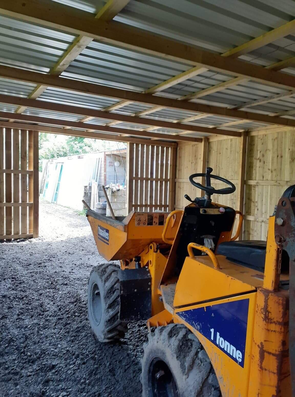 Looking out of the storage shed, mini dumper truck in shot.